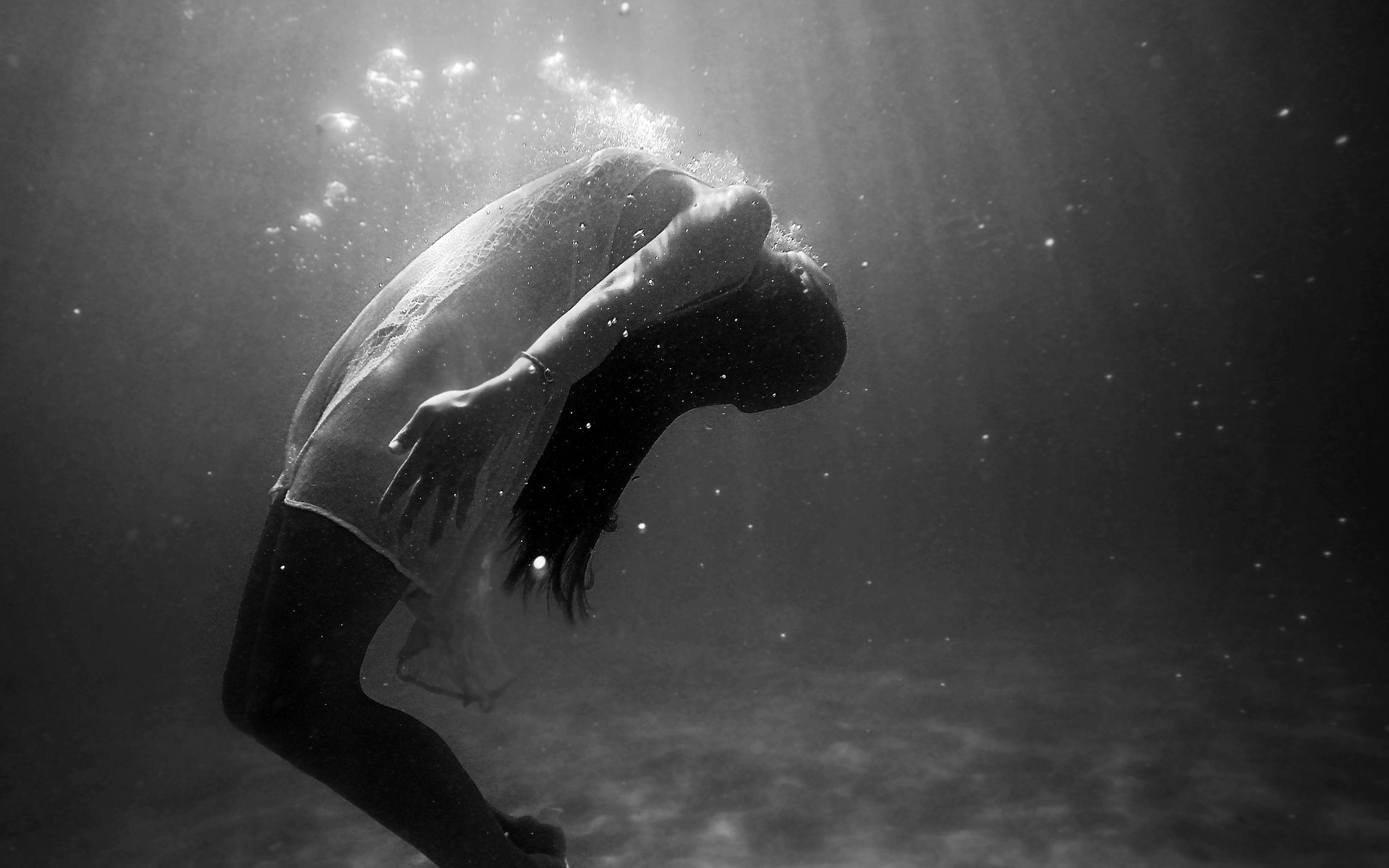 Image: Black and white photograph of a woman submerged beneath water.