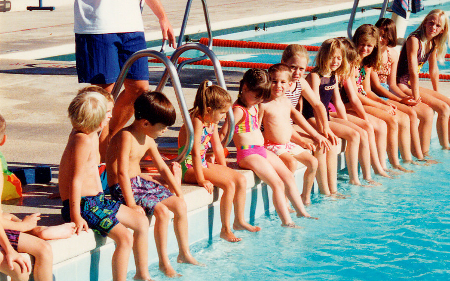 Image: A group of children sitting on the edge of a swimming pool.