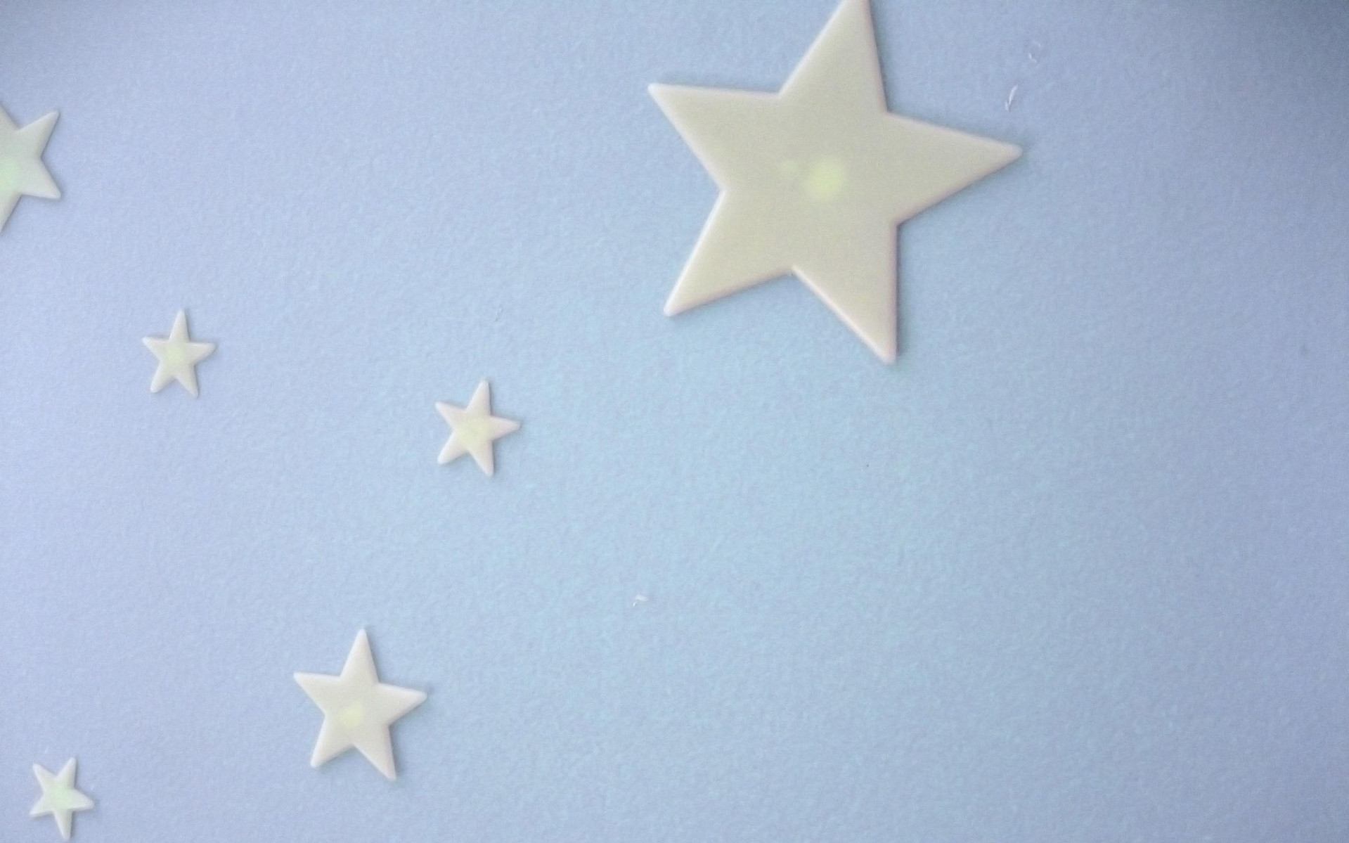 Image: A series of glow in the dark stars on a wall.