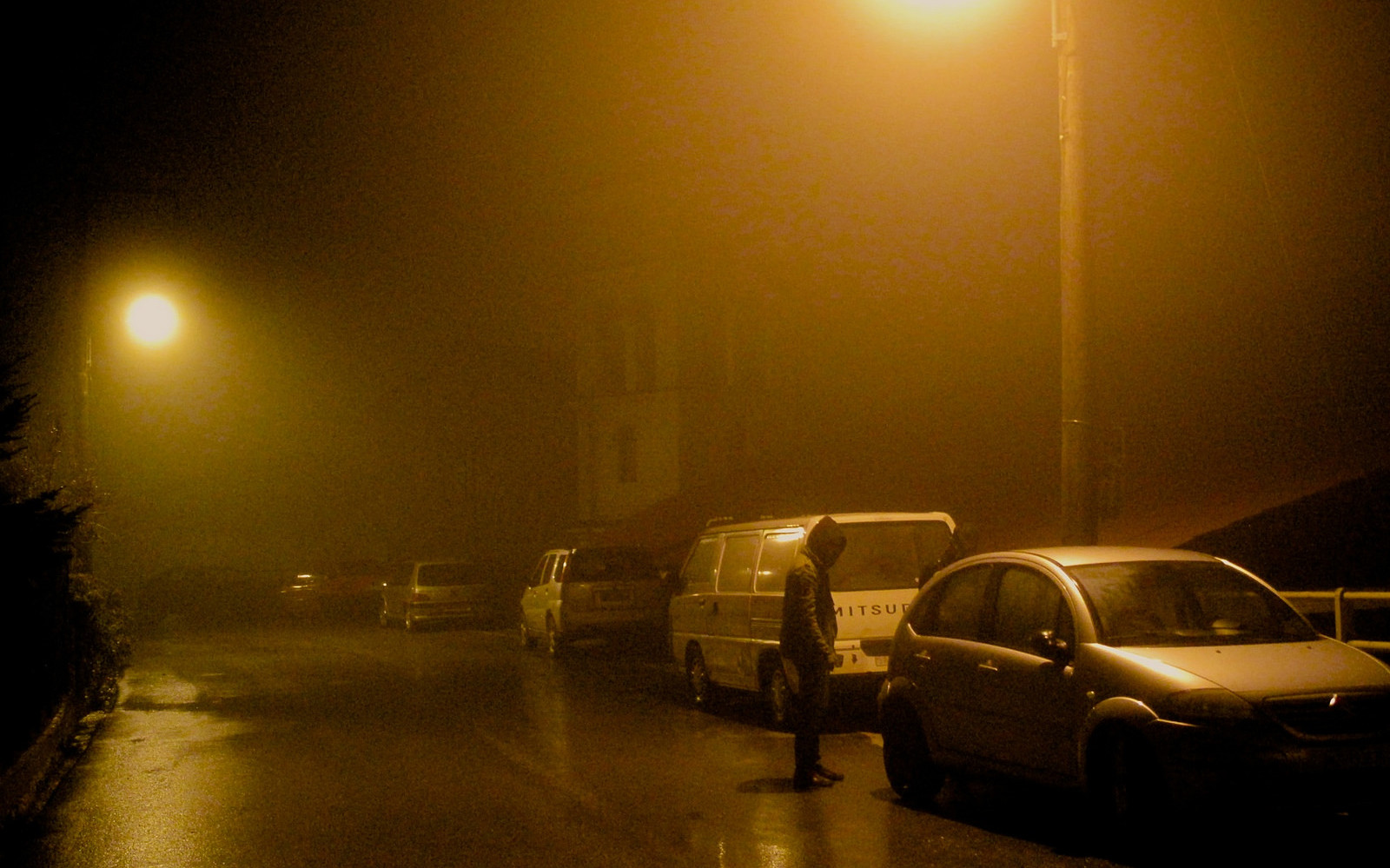 Image: A foggy/rainy city street with hooded individuals around a car.