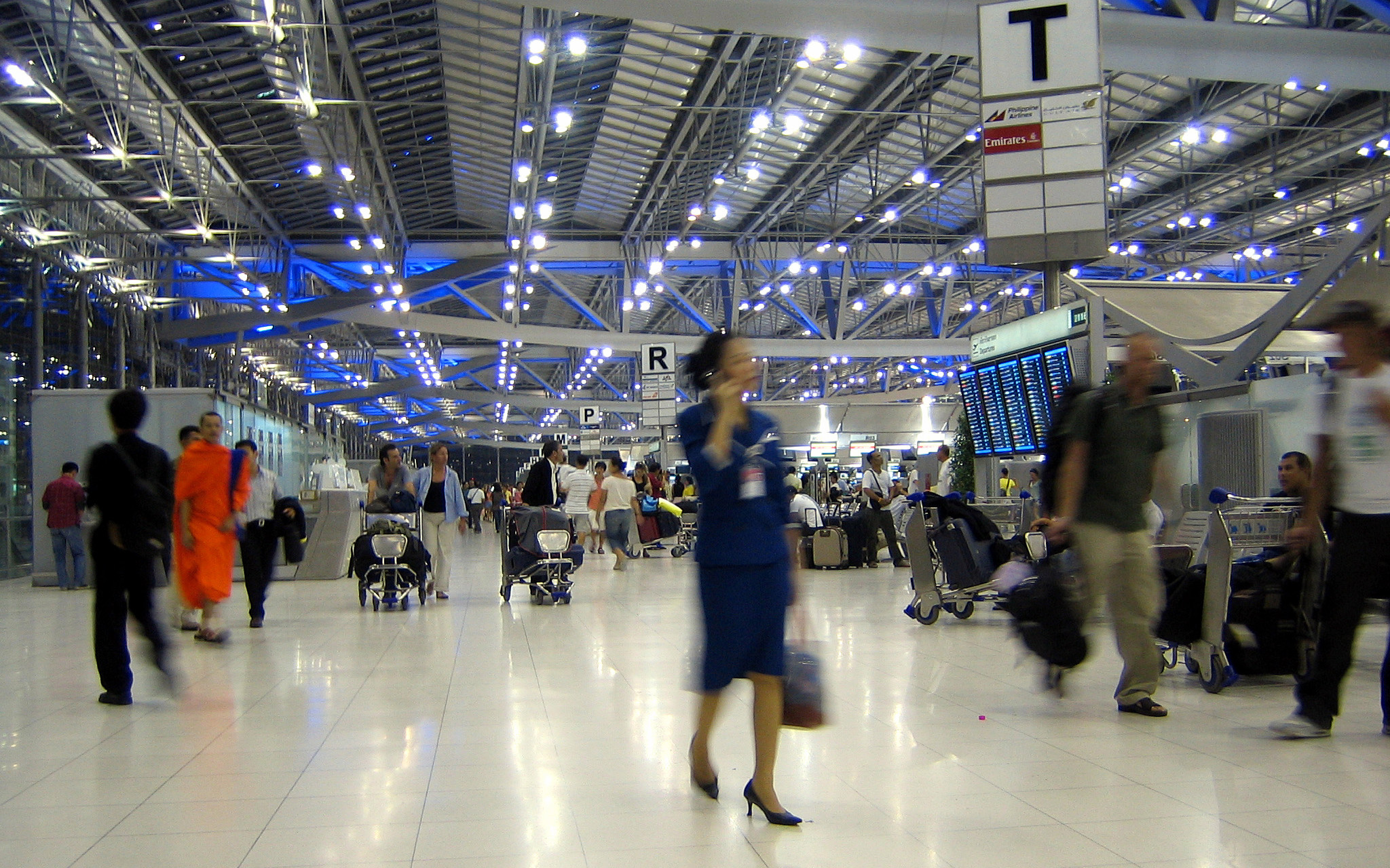 Image: People blurred and moving through a busy airport in Bangkok.