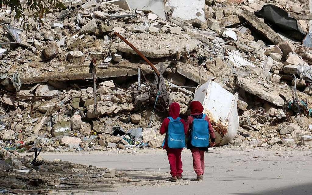 Image: Two young children walking in the rubble of a city.