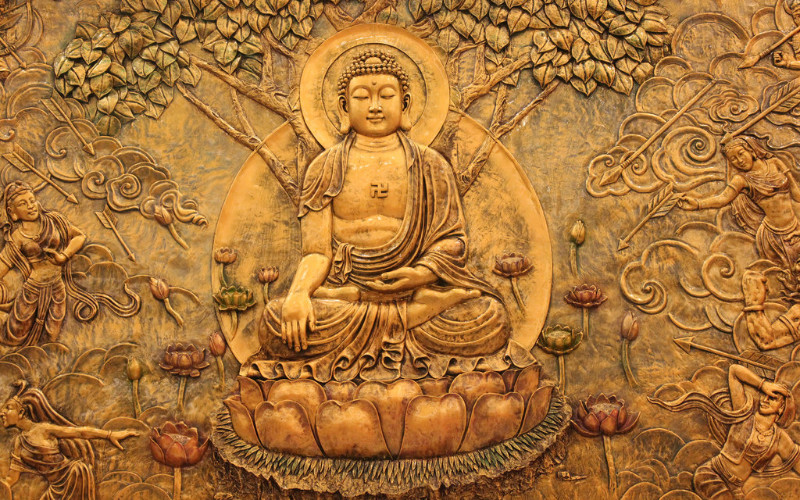 Image: A golden etching of the Buddha.