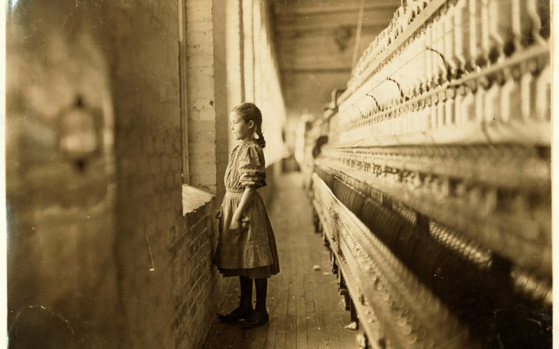 Image: A young girl staring out a window at a brick wall.