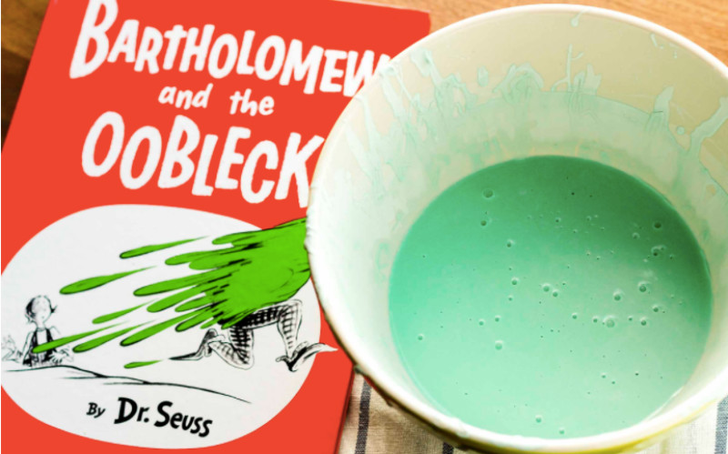Image: A cup of green oobleck next to Bartholomew and the Oobleck by Dr. Seuss