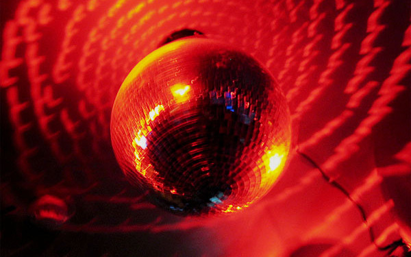 Image: A discoball in red lighting.