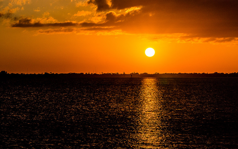 Image: The sun setting over a body of water.