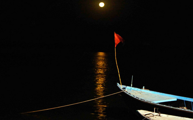 Image: A red flag on a boat in the water at night with the moon in the background