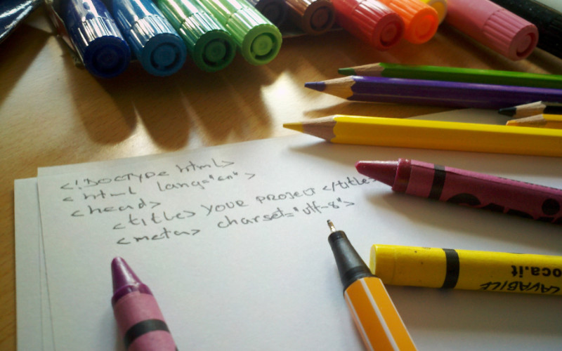 Image: Hand-written HTML code on paper surrounded by crayons, pens, and drawing implements.