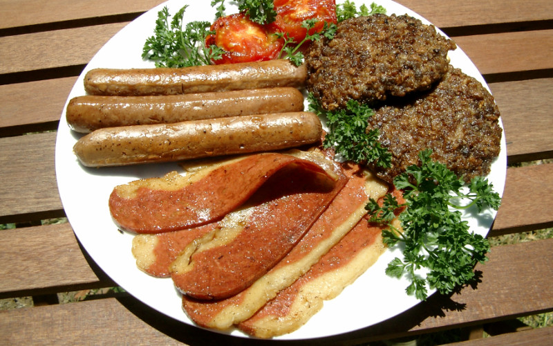 Image: A plate of vegan meat replacement, including sausage, patties, and other meats.