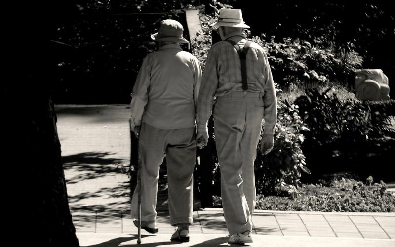 Image: Two elderly people walking away from the camera, holding hands.