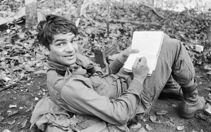 Pictured: A soldier lying down and writing on a notepad in the Vietnam war, black and white, surrounded by foliage.