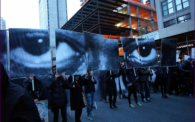 Image: A picture of protesters holding up signs that create a composite image of a face.
