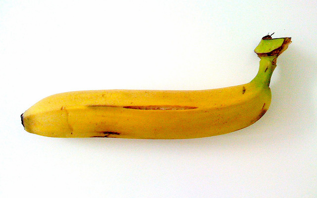 Image: A banana, skin slightly bruised and cracked.