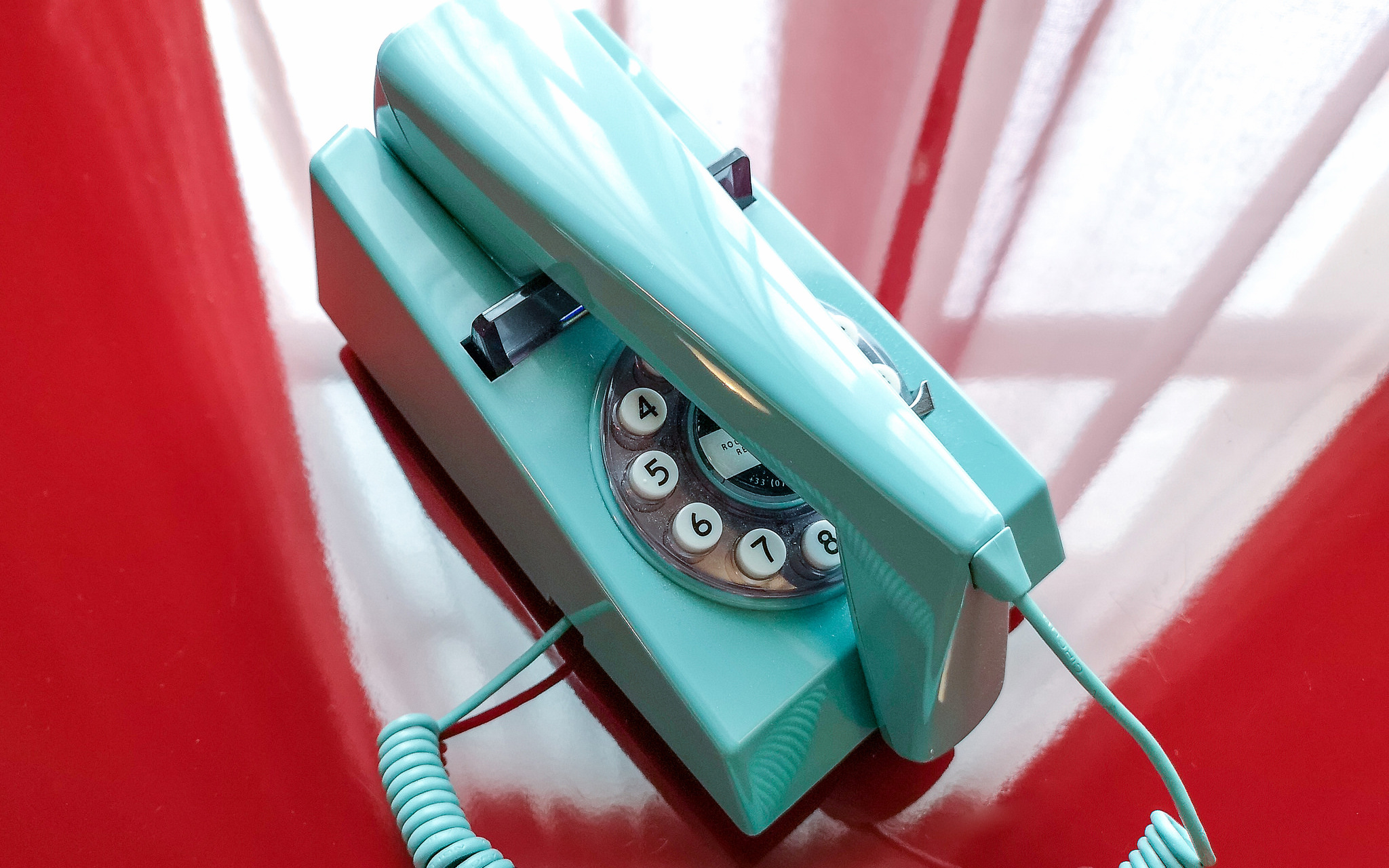"Pictured: A blue telephone upon a red table. ""Telephone"" by GillyBerlin is licensed under CC BY 2.0"