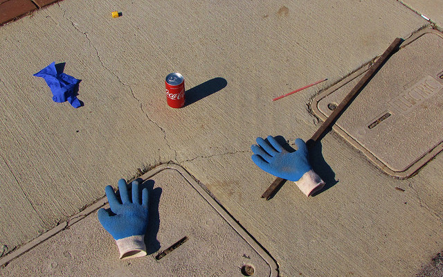 Image: Blue gloves, a stick, and a can of Coke.