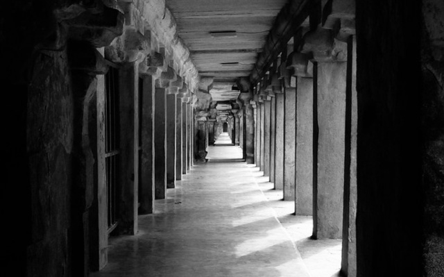 Image: Corridor and columns in black and white neo-classical style.