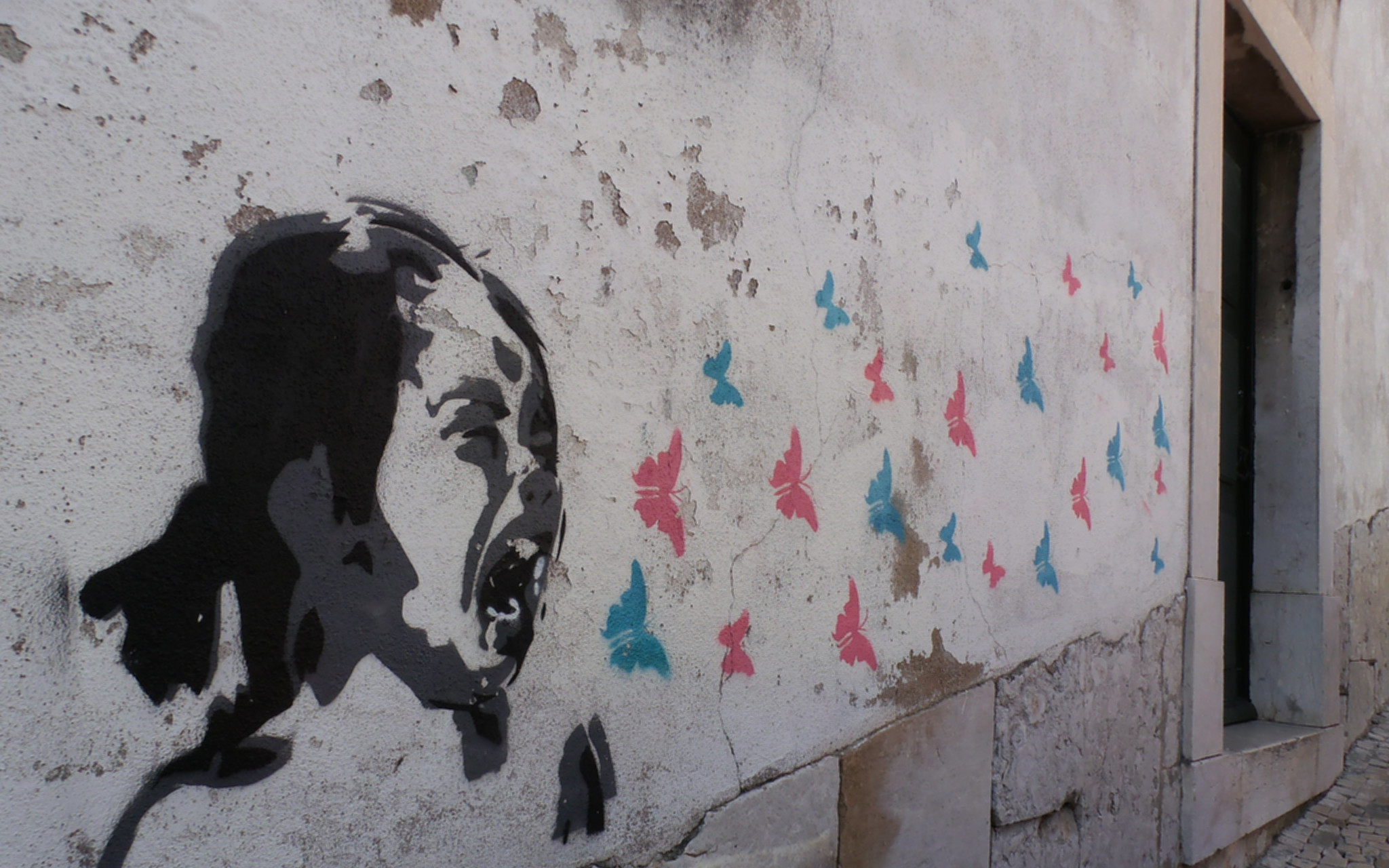A photo of street art where a young girl screams and blue and pink butterflies flutter out of her mouth